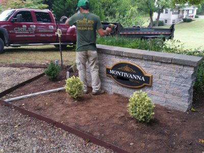 landscaper installing bushes around the Montivanna sign