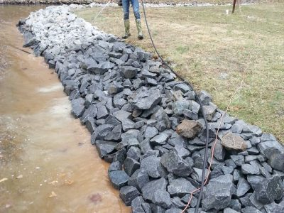 spraying a treatment on rocks in a drainage ditch