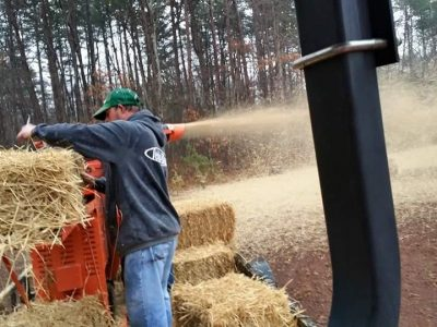 man running hay through a wood chipper for erosion control