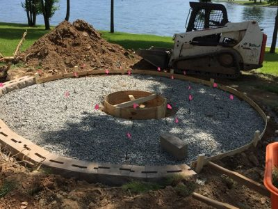 round patio being built in the middle of a yard in front of Lake Anna
