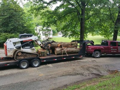 Chiles Enterprises LLC truck towing a large flatbed trailer with a cut up tree trunk and a tractor on it