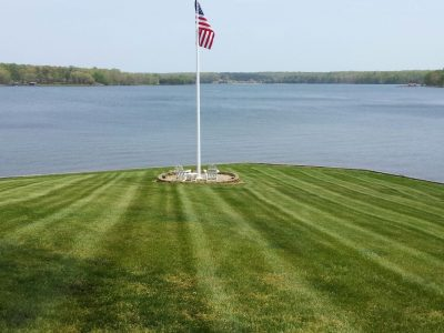 freshly mowed lawn with parallel stripes surrounding an outdoor sitting area with a flag in the middle, in front of Lake Anna