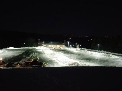 large commercial parking lot with a large snow blower clearing the snow at night