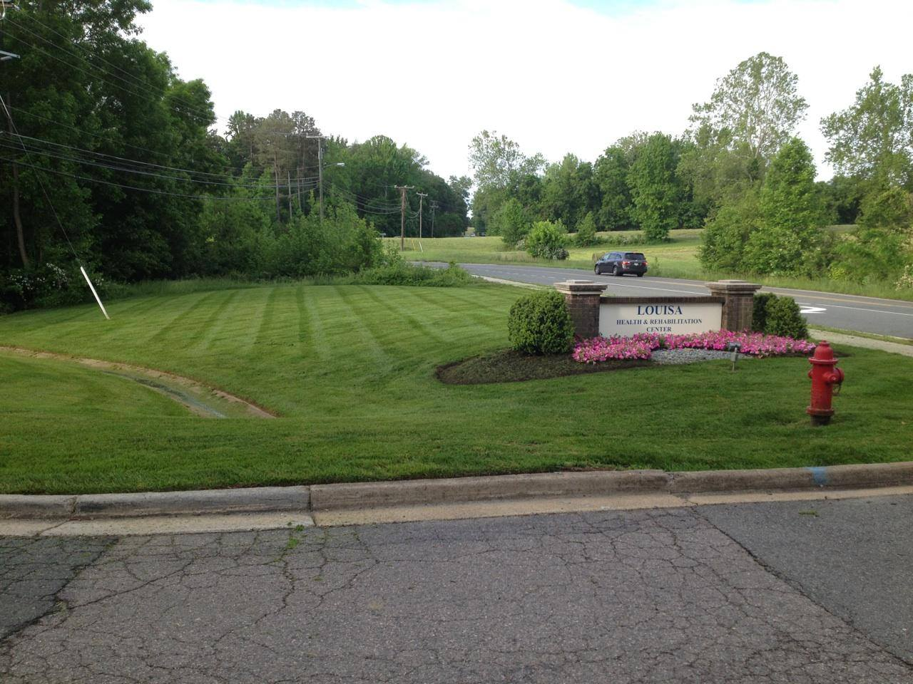 new landscape with mowed lawn and drainage and a business sign for Louisa Health and Rehabilitation Center surrounded by shrubs and flowers