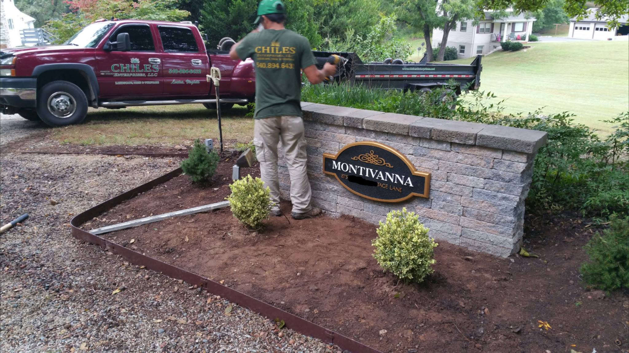 landscaper installing shrubs in front of a Montivanna sign
