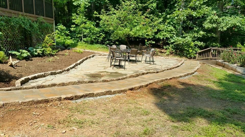 rock patio with a table and chairs next to a brick walkway leading across the yard