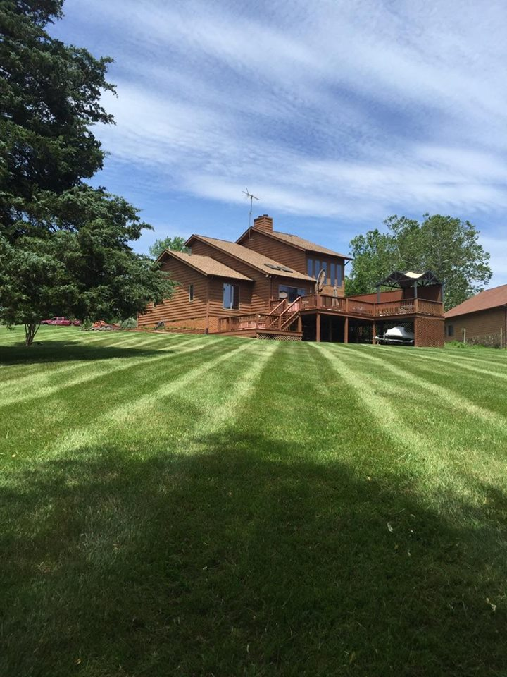 freshly cut lawn with parallel stripes and a brown house in the background